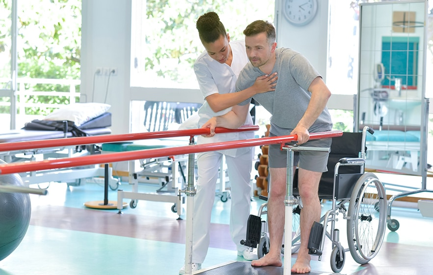 Laufunterstützung in einer Reha, Patient wird gestützt